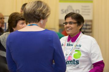 Woman wearing Healthwatch clothing talking to another woman