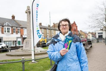 Woman stood in front of a Healthwatch flag holding up a leaflet about volunteering