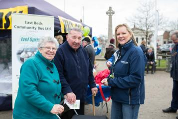 Woman wearing a Healthwatch jacket stood with two members of the public