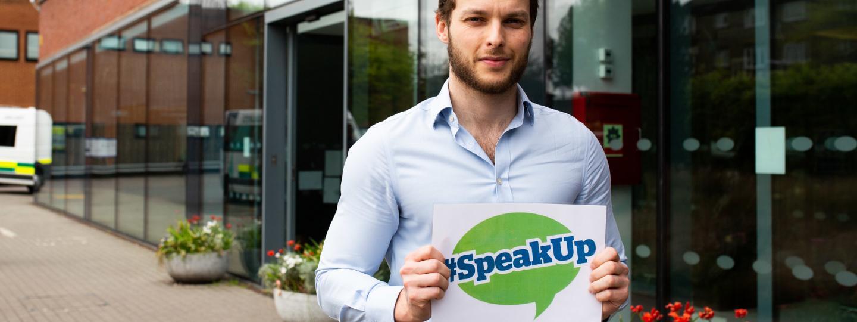 Man holding healthwatch speak up sign