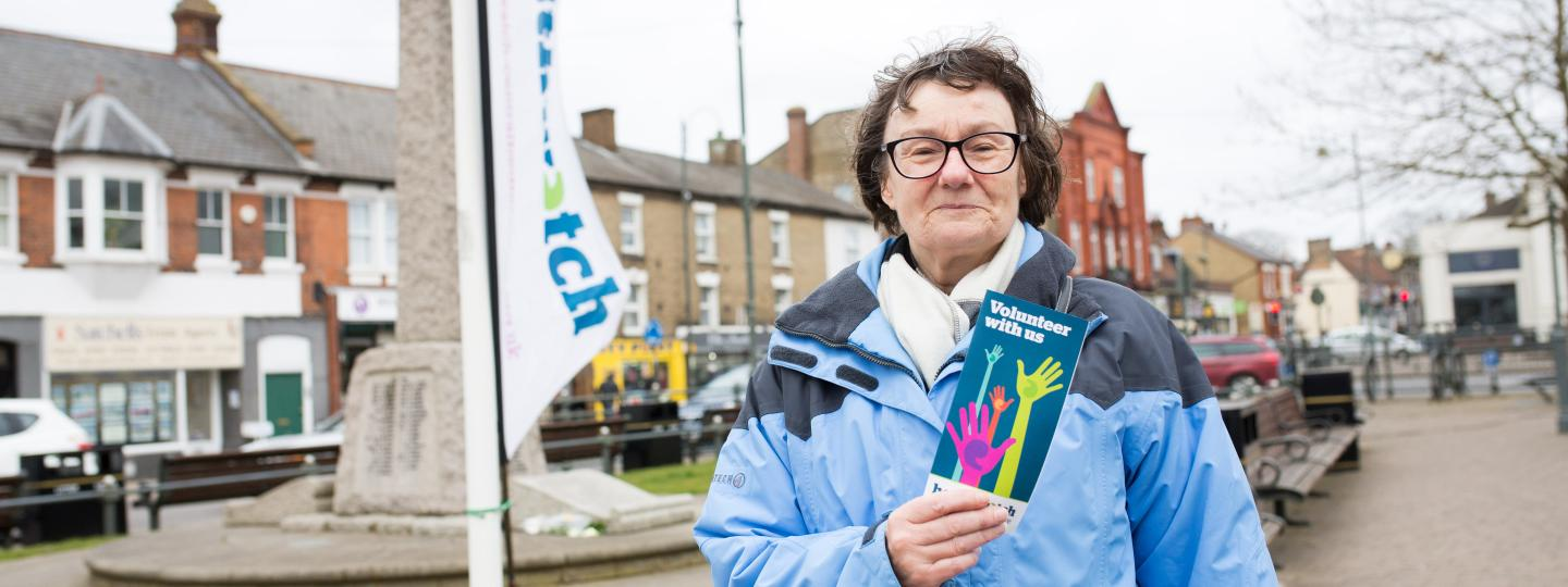 Volunteer infront of a Healthwatch flag holding a leaflet about volunteering